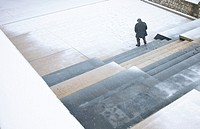 Old man walking under a snowfall on a park in Morella