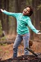 Young African American child outside in a wooded area with both arms outstretched and she is singing.