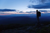 A hiker ascending the Jewell Trail enjoys the views at sunset  Located in the White Mountains, New Hampshire USA