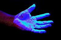 Hand covered in UV sensitive solution under Ultra Violet light source to detect germs and other undesirable materials to be washed off  before proceed...