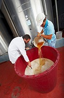 Agronomist and his assistant prepare a solution with water and yeast to be injected into a large tank containing wine