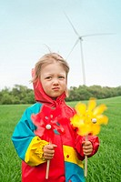 boy in colorful raincoat holding pinwheel standing in front of wind turbine