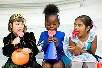 Little girls dressed in Halloween costumes enjoy their lollipops