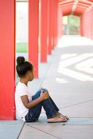 A mixed race little black girl quitely sits in a school yard