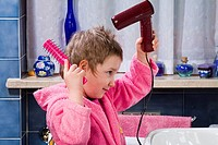 Child who dries her hair and comb with a hairbrush