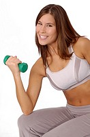 Attractive woman sitting and exercising with hand weight