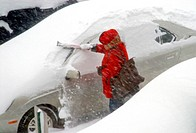 Woman clearing heavy snowfall from car during storm