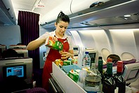 Long haul flight air stewardess with food drinks aisle trolley on Virgin Atlantic airline aircraft serving drink to passenger