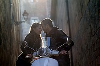 Couple embracing and leaning on a motor scooter