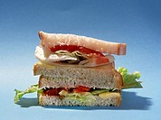 close view of a salad sandwich on a plain blue background