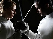 Two fencers, a young woman and a young man, confronting each other with their fencing epees crossed