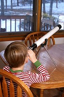 Little boy inside looking outside in winter through a telescope