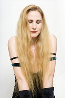 A fair skinned woman with very long blond hair has her eyes closed as she kneels on the floor.