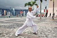 Portrait of Tai Chi master Mr  Ng at a shadow boxing posture shoot at the Avenue of Stars with Hong Kong's skyscrapers noticeable at the background , ...