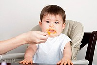 Cute baby infant boy girl expresses dislike disgust for food fed by spoon