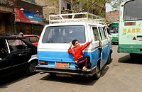 little egyptian boy hitching a lift on the back of a taxi bus , souk goma friday market , street market , Southern Cemeteries , Khalifa district , cai...