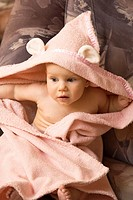 Emotional Eight Month Old Infant Girl Sitting in Bathrobe