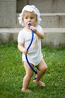 One Year Old Baby Girl Standing Outside and Blowing into Tube
