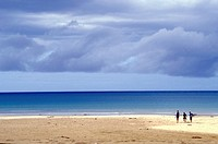 Vast expanse of open beach along the southern Australian coastline with three surfies seen in the distance enjoying the freedom af the wide open space...