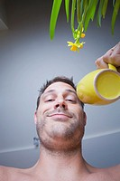Man in his kitchen drinking coffee from a yellow mug