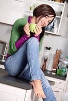 woman in kitchen drinking hot beverage