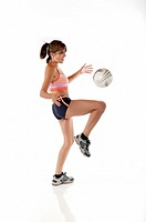 Hispanic woman juggling soccer ball