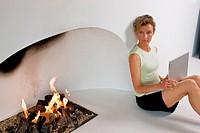 Woman sitting by fireplace, using laptop