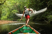 Iban man casts his fishing net in Batang Ai National Park in Sarawak, Borneo, Malaysia