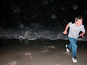 Young Boy running from wave