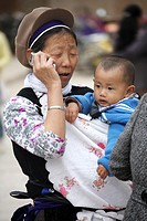 A Bai nationality lady carrying a baby and talk on a cell phone  Kunming  China.