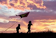 A brother and sister getting a kite to fly suring sunset