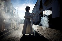 A female acolyte spreads incense during an Easter Holy Week procession in Prado del Rey, Andalusia, Spain, April 24, 2011