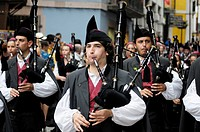 Parade of pipe bands through the streets of Llanes during the festival of San Roque, Llanes, Asturias, Spain.