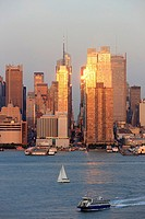 The setting sun reflects off the windows of Manhattan skyscrapers on 42nd street in New York City, New York, USA as viewed over the Hudson River from ...