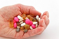 UK, Britain, Europe Elderly woman holding a selection of prescription and supplement pills in the palm of one hand
