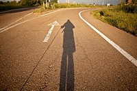 Early morning shadow of a hiker and white arrow on road along the Camino de Santiago
