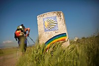 Pilgrim and marker with rainbow along the Camino de Santiago