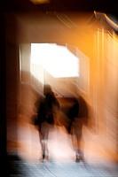 abstract two people walking in dark corridor at night