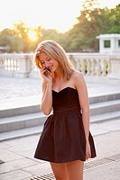 Cute young blonde woman in a black elegant dress talking on her phone