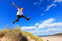 boy jumping from dunes Sutherland, Scotland
