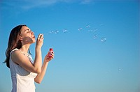 Young woman blowing bubbles against blue sky, close-up