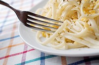 closeup of a plate of pasta on a checkered tablecloth