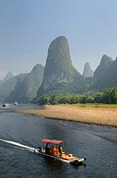 Tour boat raft traveling down the Li river with tall karst mountain cones in background. Guangxi, China.