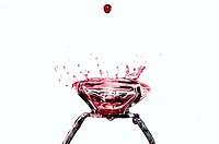 Red water drops falling on a diamond ring