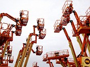 Industrial aerial work platforms facing eachother like getting into a clash against white background in Dordrecht, Zuid Holland, The Netherlands