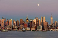 The waxing gibbous moon sits high in the magenta colored twilight sky over the New York City skyline the day before the full moon, as the orange glow ...