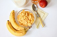 Breakfast cornflakes with milk and fruit  Cornflakes with bananas for healthy breakfast  Juice in lead glass  Nectarine  Yellow napkin with yellow fla...