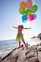 little girl holding balloons and jumping while on the rocks at the ocean