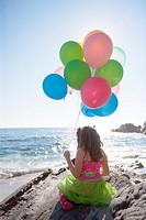 little girl sitting on rocks, holding balloons, overlooking the ocean