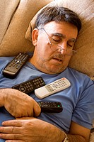 Man asleep with television remote controls